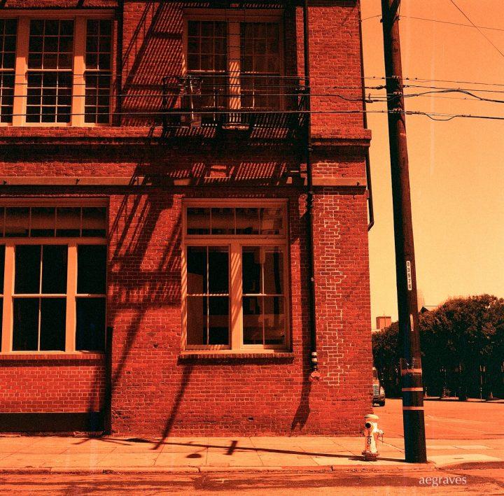 Red tinted image of brick industrial building corner